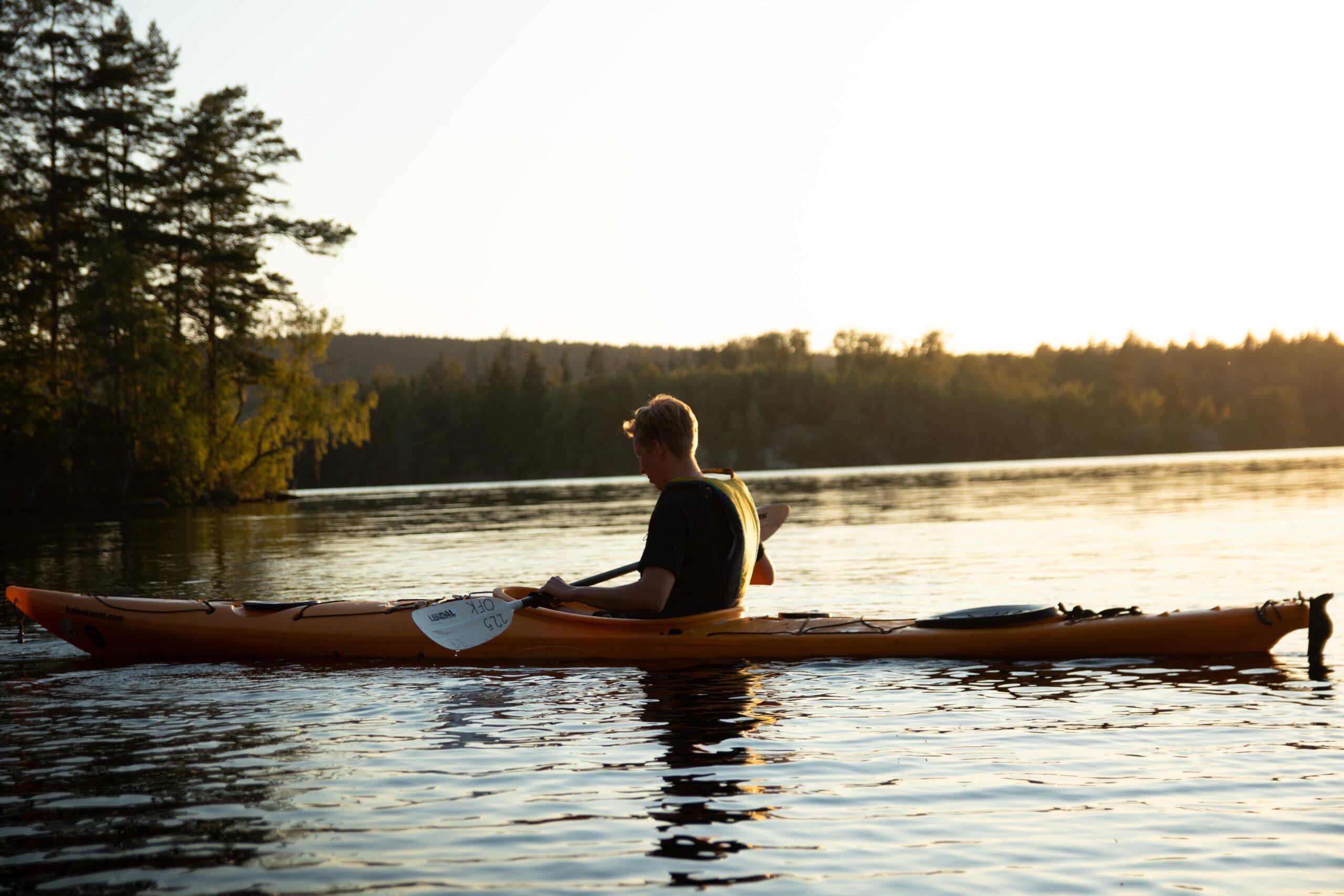 Man i kajak ute på vattnet